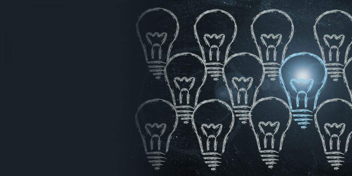 chalk drawings of a panel of light bulbs with one lit representing an idea